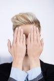 女实业家掩藏的面孔用手在办公室 库存图片