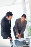 女实业家显示合作伙伴在哪里签字 免版税库存照片
