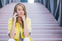 年轻女实业家有交谈使用在电话的一个智能手机,当坐桥梁时 库存照片