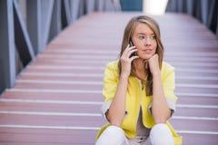 年轻女实业家有交谈使用在电话的一个智能手机,当坐桥梁时 库存图片