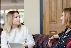 年轻女实业家有交谈在非正式会议上 库存照片