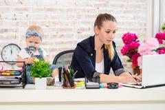 女实业家有工作在膝上型计算机的女儿的母亲妇女 库存图片