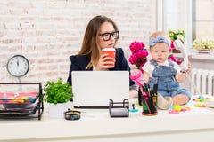 女实业家有工作在计算机的女儿的母亲妇女 库存图片