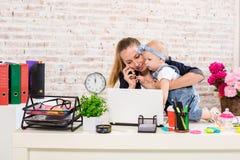 女实业家有工作在计算机的女儿的母亲妇女 免版税图库摄影
