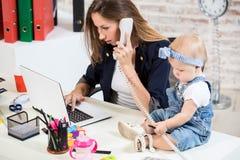 女实业家有工作在计算机的女儿的母亲妇女 图库摄影