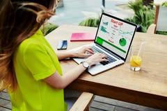 女实业家有财政信息的前面便携式计算机作为图表和图坐屏幕 图库摄影