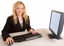 女实业家服务台她微笑的工作 免版税库存照片