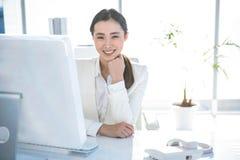 女实业家服务台她微笑的工作 免版税图库摄影