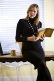 女实业家服务台注意怀孕的文字 免版税库存图片