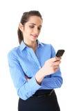 女实业家检查她的移动电话,查出在白色 免版税库存照片