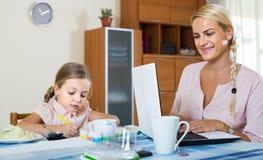 女实业家浏览互联网在家,在p的女儿图画 图库摄影