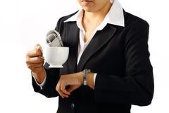女实业家用咖啡和看她的手表 免版税库存照片