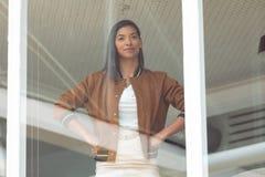 女实业家用在站立在窗口附近的臀部的手在一个现代办公室 免版税图库摄影