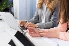 女实业家用途键入在键盘,配合概念,露天场所办公室两女商人的便携式计算机工作  库存图片