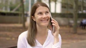 女实业家画象坐在公园的白色衬衣的 使用手机的专业女性 股票视频