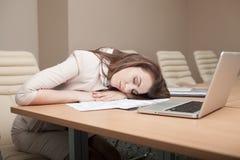 女实业家疲倦于与膝上型计算机一起使用 免版税库存照片