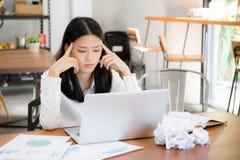 女实业家疲倦和注重与劳累过度在书桌,妇女亚洲人有与图表分析膝上型计算机的不是担心的想法 库存照片