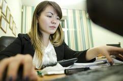 女实业家的画象坐她的工作场所在办公室,键入,看个人计算机屏幕 免版税库存照片