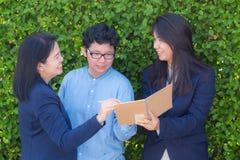 女实业家看关于笔记本或日志的三个人信息公司在树墙壁上 库存照片