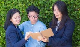 女实业家看关于笔记本或日志的三个人信息 库存图片
