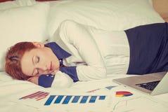 女实业家睡着在床、旅馆或者国内屋子上 库存图片