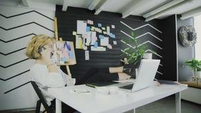 女实业家移动式摄影车移动谈话在电话和与腿坐桌 股票视频