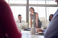 女实业家站立听同事在会议上 免版税库存照片