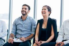 女实业家笑和听乐趣介绍和研讨会在旁边与男性企业工友 库存图片