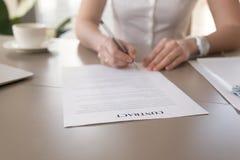 女实业家签署的文件,投入署名的女性手, 免版税库存图片