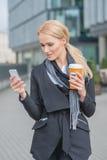 女实业家繁忙与电话,当食用咖啡时 库存图片