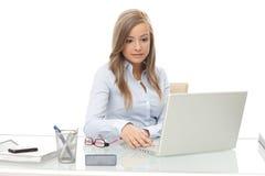 年轻女实业家繁忙通过工作在书桌 免版税图库摄影