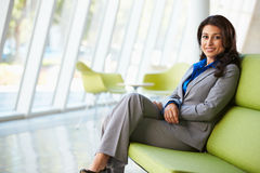 女实业家纵向坐沙发在现代办公室 免版税库存图片