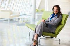 女实业家纵向坐沙发在现代办公室 免版税库存照片