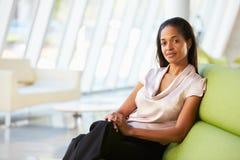 女实业家纵向坐沙发在现代办公室 库存照片