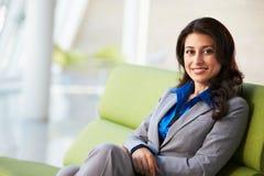 女实业家纵向坐沙发 免版税图库摄影