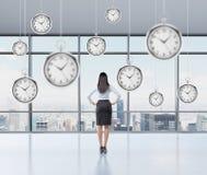 女实业家考虑时间的,盘旋的怀表上面 免版税图库摄影