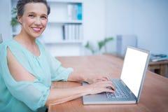 女实业家膝上型计算机微笑的工作 免版税库存照片