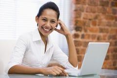 女实业家膝上型计算机笑的办公室 免版税库存照片