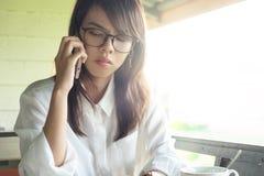 女实业家装备玻璃谈话在电话在办公室外 Thi 免版税库存照片
