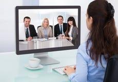 女实业家观看的电视电话会议 图库摄影