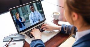 女实业家视讯会议大角度看法在膝上型计算机的在书桌 库存照片