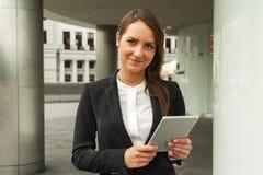 年轻女实业家触板在城市 微笑 免版税库存照片