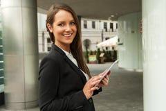 年轻女实业家触板在城市 微笑 库存图片