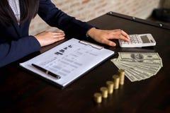 女实业家计算从出口业务的收入在木桌上 到达天空的企业概念金黄回归键所有权 库存照片
