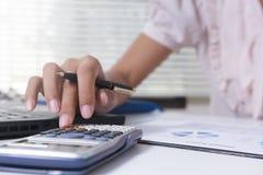 女实业家计算关于费用,并且做财务在办公室,财务经理分配,概念事务和财务投资 免版税库存照片