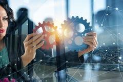 女实业家设法连接齿轮片断 配合、合作和综合化的概念 两次曝光 库存例证
