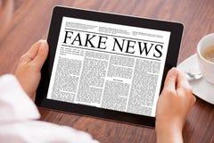 女实业家读书在数字式片剂的伪造品新闻在表上 免版税库存图片