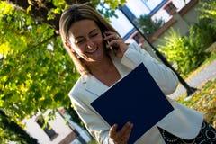 女实业家读书报告,当谈话在手机本质上时 免版税库存图片