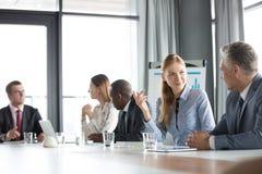 年轻女实业家谈论与男性同事在证券交易经纪人行情室 免版税库存图片