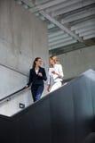 女实业家谈论在数字式片剂,当走在楼梯时 库存照片